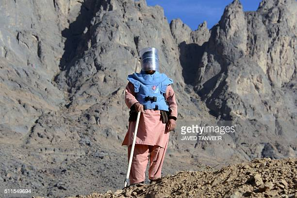An Afghan demining security personnel looks on during an operation to clear mines from a field in the Panjwai district of Kandahar province on...