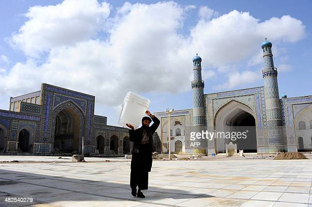 An Afghan election worker carries a plastic box containing election material into a polling station at Jamee mosque in the northwestern city of Herat...