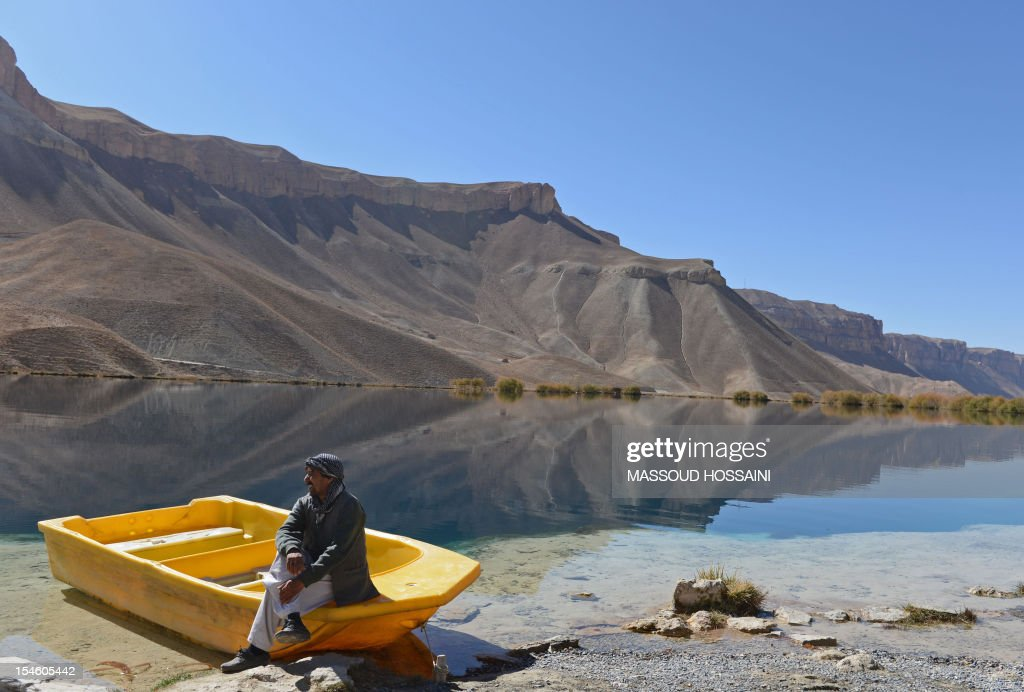 An Afghan ethnic Hazara tribesman sits on a boat at the Band-e Amir lake in Bamiyan province on October 23, 2012. Bamiyan, some 200 kilometres (124 miles) northwest of Kabul, stands in a deep green and lush valley stretching 100 kilometres through central Afghanistan, on the former Silk Road that once linked China with Central Asia and beyond. The town was home to two nearly 2,000-year-old Buddha statues before they were destroyed by the Taliban, months before their regime was toppled in a US-led invasion in late 2001. AFP PHOTO / Massoud HOSSAINI