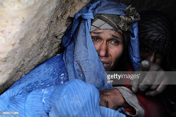 An Afghan female drug addict looks out from her hut during snowfall on the outskirts of Herat on February 1 2014 As winter sets in across Central...