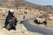 An Afghan fighter belonging to the Taliban Islamic militia guards a road southeast of Kabul after Taliban troops drove into the area with no...
