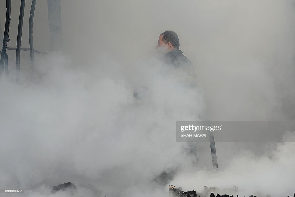 An Afghan firefighter walks past smoke and smouldering debris at the scene after a huge fire swept through a market in Kabul on December 23, 2012. A huge fire swept through a market in downtown Kabul on December 23, destroying hundreds of shops and forcing the city's nearby money exchange to evacuate, police and witnesses said. There were no reports of any casualties in the early morning blaze which destroyed most of the cloth market's 500 shops, Kabul fire department officials told AFP. AFP PHOTO/ SHAH Marai