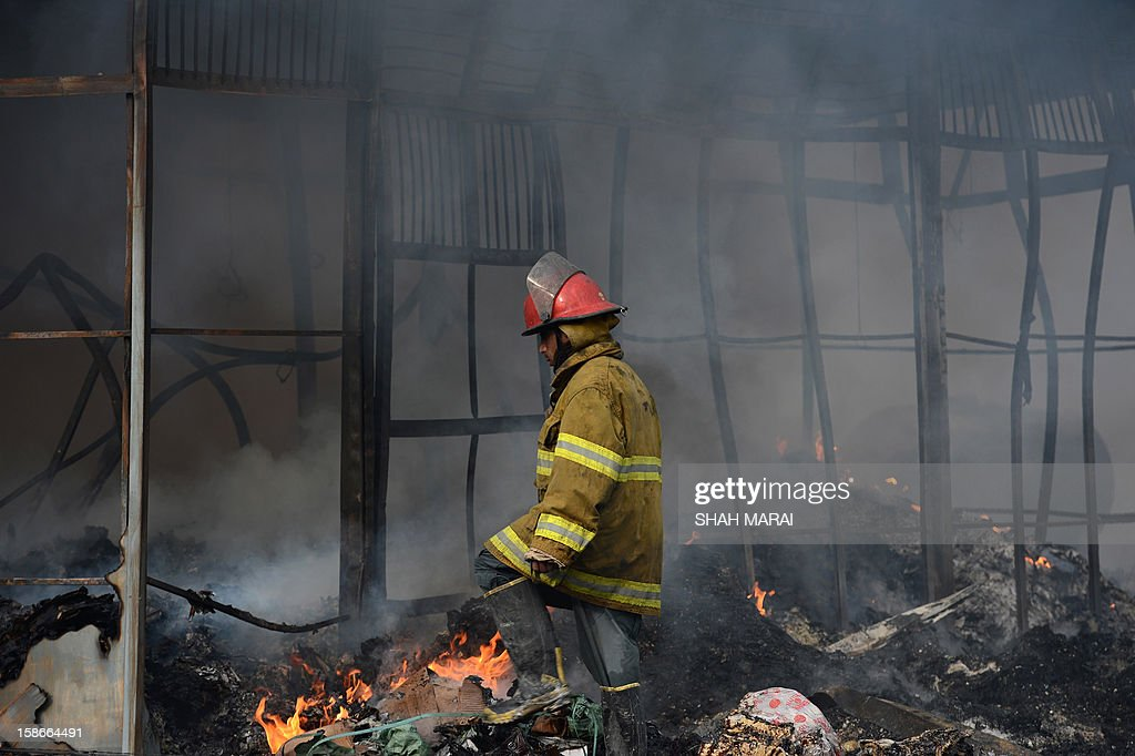 An Afghan firefighter walks past smouldering shopfronts after a huge fire swept through a market in Kabul on December 23, 2012. A huge fire swept through a market in downtown Kabul on December 23, destroying hundreds of shops and forcing the city's nearby money exchange to evacuate, police and witnesses said. There were no reports of any casualties in the early morning blaze which destroyed most of the cloth market's 500 shops, Kabul fire department officials told AFP. AFP PHOTO/ SHAH Marai