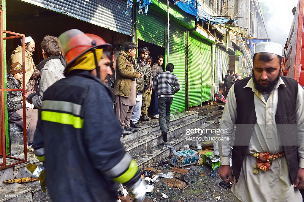 An Afghan firefighter walks through a market that was destroyed by a fire in Kabul on December 23, 2012. A huge fire swept through a market in downtown Kabul on December 23, destroying hundreds of shops and forcing the city's nearby money exchange to evacuate, police and witnesses said. There were no reports of any casualties in the early morning blaze which destroyed most of the cloth market's 500 shops, Kabul fire department officials told AFP. AFP PHOTO/ Massoud HOSSAINI