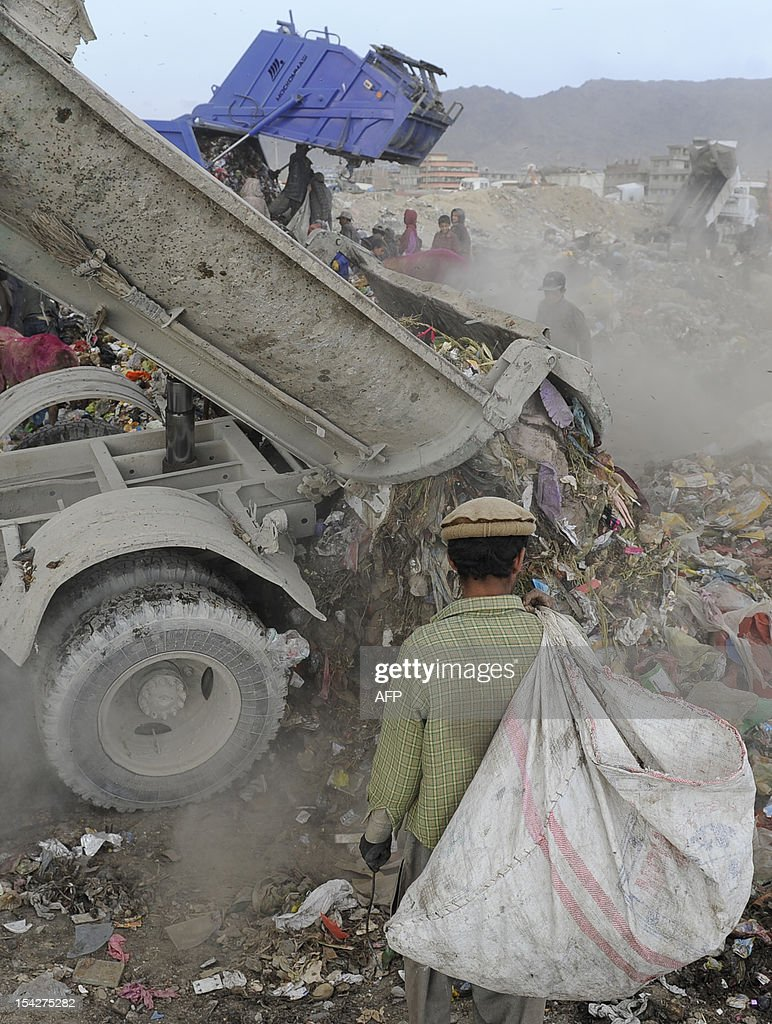 An Afghan garbage collector looks for recyclable material from a landfill in the outskirts of Kabul on October 17, 2012. Over a third of Afghans are living in abject poverty, as those in power are more concerned about addressing their vested interests rather than the basic needs of the population, a UN report said.