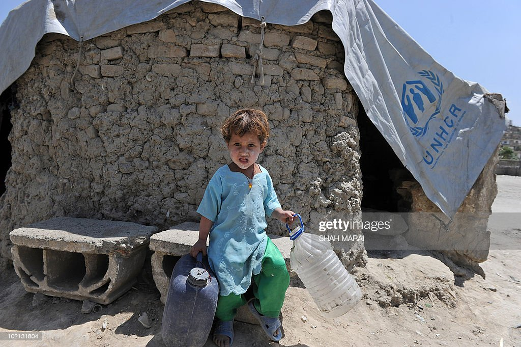 An Afghan girl carries plastic vessels as she sits beside a tent in Kabul on June 16, 2010. Afghanistan is one of the world's poorest countries where unemployment is at 40 percent and half the population is under the poverty line. AFP PHOTO/SHAH Marai