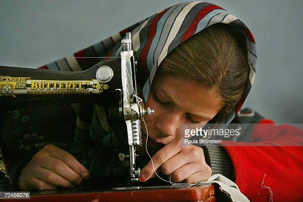An Afghan girl learns to use a sewing machine at the International Orphan Care center January 21 2003 in Kabul Afghanistan The privately funded...