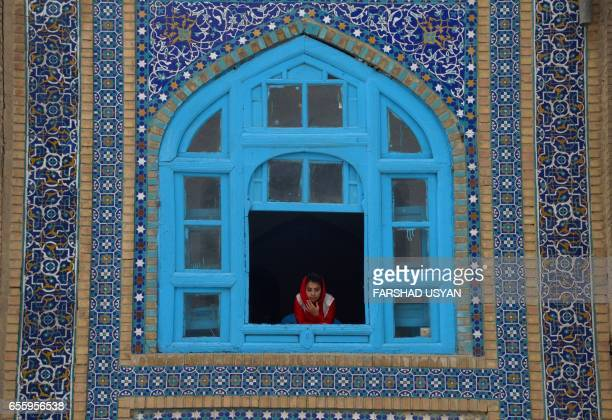 TOPSHOT An Afghan girl looks on a window of the HazrateAli shrine at Nowruz festivities which mark the Afghan new year in MazariiSharif on March 21...