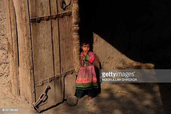 TOPSHOT An Afghan girl looks on as a health worker administers polio vaccine drops to others during a vaccination campaign on the outskirts of...