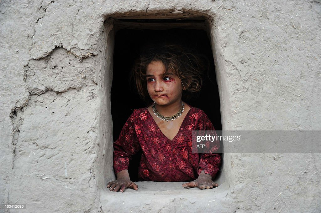 An Afghan girl looks out of her window near an open classroom on the outskirts of Jalalabad on January 30, 2013. Afghanistan has had only rare moments of peace over the past 30 years, its education system being undermined by the Soviet invasion of 1979, a civil war in the 1990s and five years of Taliban rule. AFP PHOTO/ Noorullah Shirzada