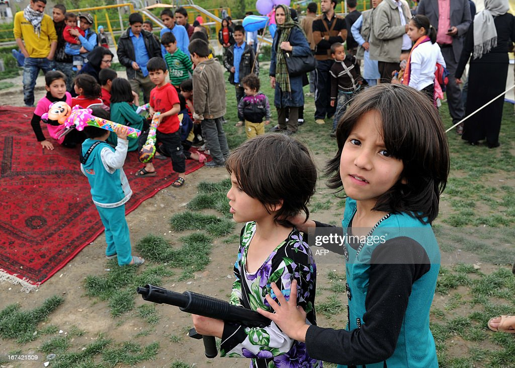 An Afghan girl plays with a toy gun along with a friend as she takes part in a book reading event held by the Goethe-Institut as part of ongoing World Book Day celebrations in Kabul on April 25, 2013
