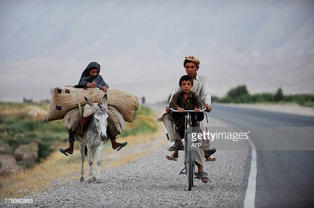 An Afghan girl rides a donkey alongside her brothers on a bicycle at Sholgara district on the outskirts of Mazarisharif on August 2 2013 Economic...