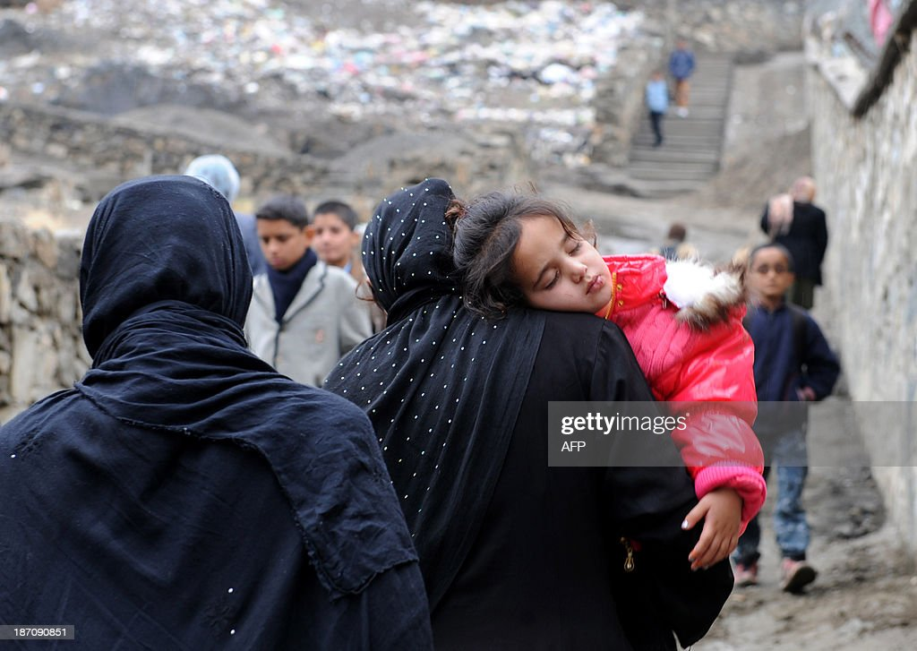 An Afghan girl sleeps as she is carried by her mother on a rainy day in Kabul on November 6, 2013. Despite massive injections of foreign aid since the fall of the Taliban in 2001, Afghanistan remains desperately poor as it attempts to recover from decades of conflict. AFP PHOTO / Farshad USYAN