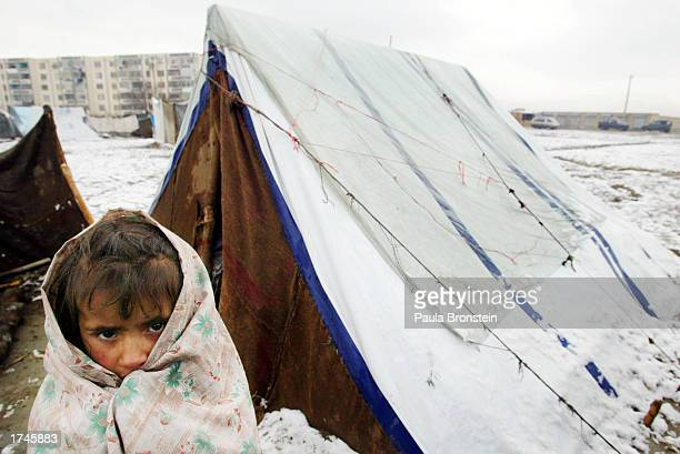 An Afghan girl tries to keep warm outside her family's tent during the first snowfall this winter January 26 2003 on the outskirts of Kabul...