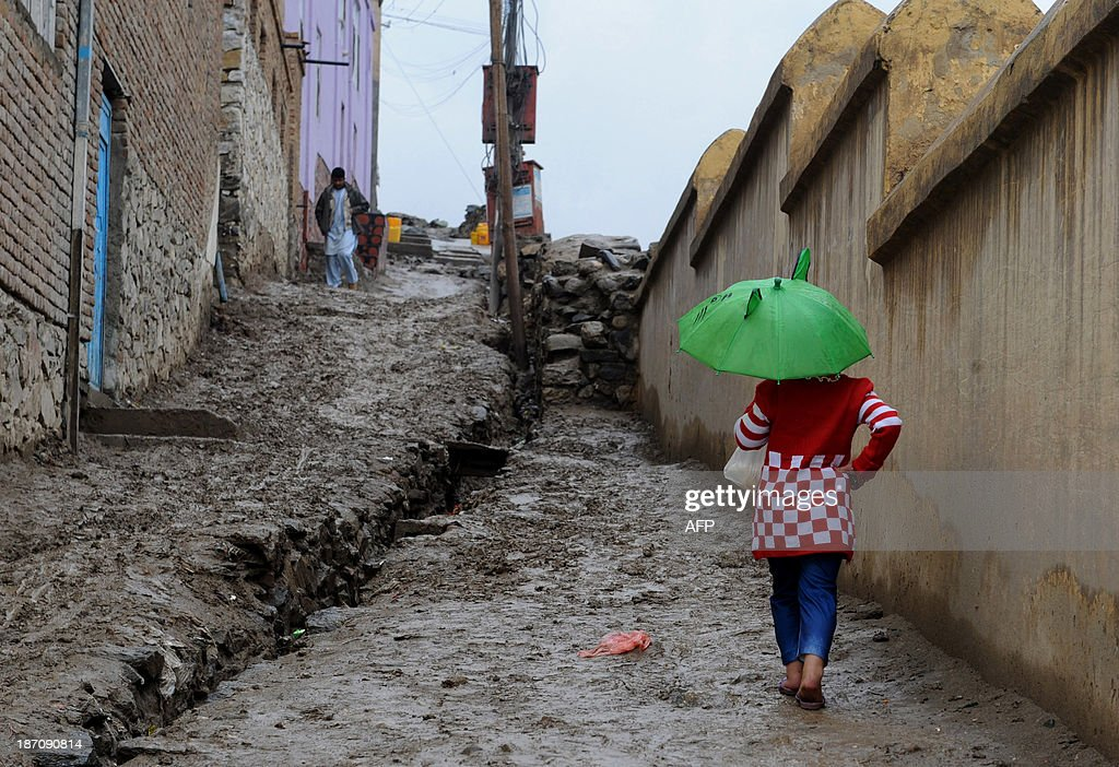An Afghan girl walks through her neighbourhood holding a small umbrella on a rainy day in Kabul on November 6, 2013. Despite massive injections of foreign aid since the fall of the Taliban in 2001, Afghanistan remains desperately poor as it attempts to recover from decades of conflict. AFP PHOTO / Farshad USYAN