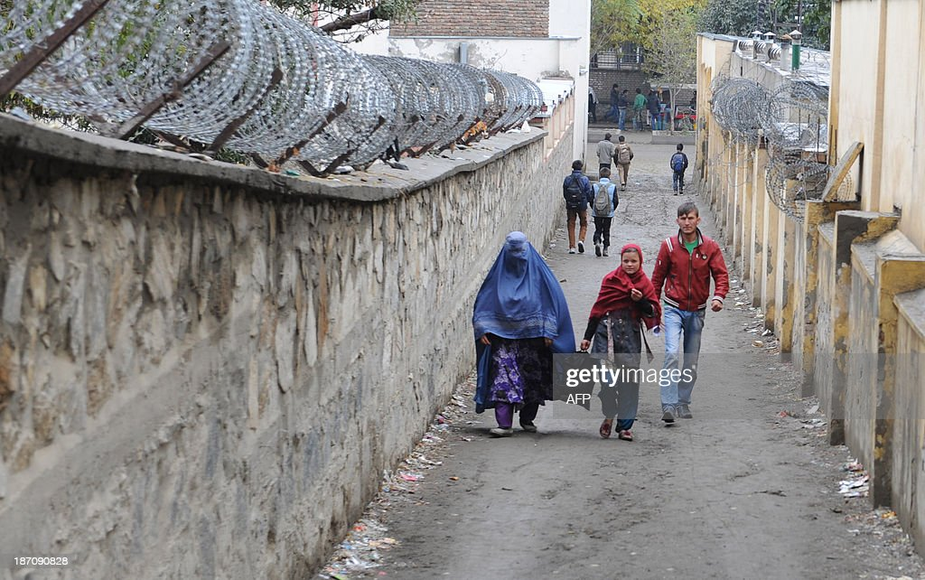 An Afghan girl walks with her mother on a rainy day in Kabul on November 6, 2013. Despite massive injections of foreign aid since the fall of the Taliban in 2001, Afghanistan remains desperately poor as it attempts to recover from decades of conflict. AFP PHOTO / Farshad USYAN