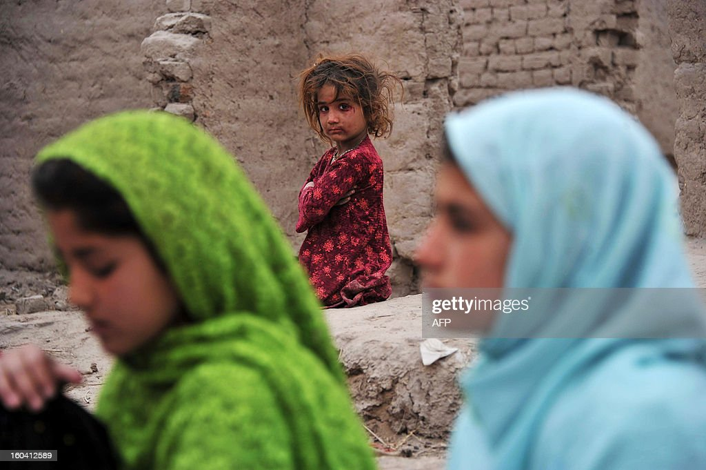 An Afghan girl watches other schoolgirls study at an open classroom in the outskirts of Jalalabad on January 30, 2013. Afghanistan has had only rare moments of peace over the past 30 years, its education system being undermined by the Soviet invasion of 1979, a civil war in the 1990s and five years of Taliban rule. AFP PHOTO/ Noorullah Shirzada