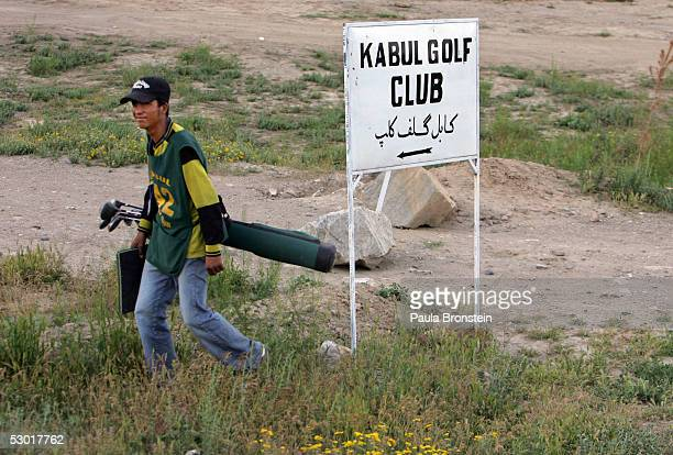 An Afghan golfer walks towards the course armed with golf clubs at the Kabul Golf Club June 3 2005 in Kabul Afghanistan The Kabul Golf Club has been...