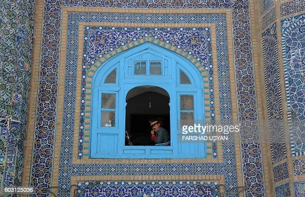 An Afghan guard of honour looks out as other offer EidalAdha prayers at the Hazrati Ali shrine in Mazari Sharif on September 12 2016 Afghans started...