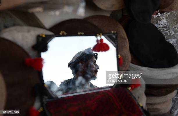 An Afghan hat vendor waits for customers at a market in preparation for the holy month of Ramadan in Kabul on June 26 2014 Islam's holy month of...