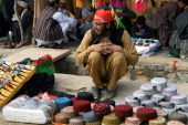 An Afghan hat vendor waits for customers at a roadside shop in Kandahar on March 21 2014 Afghanistan's economy has improved significantly since the...
