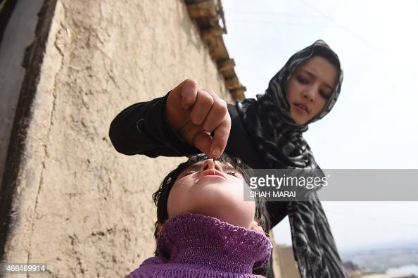 An Afghan health worker administers polio vaccine drops to a child on the second day of a vaccination campaign in Kabul on March 16 2015 Nearly nine...