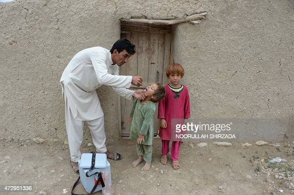 An Afghan health worker administers the polio vaccine to a child during a campaign at a refugee camp on the outskirts of Jalalabad in Nangarhar...
