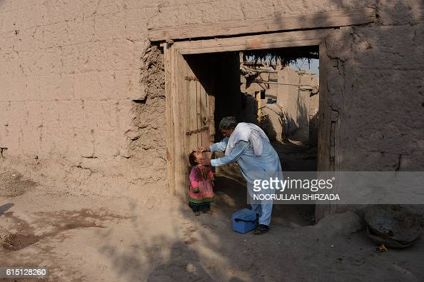 An Afghan health worker administers the polio vaccine to a child during a campaign on the outskirts of Jalalabad on October 17 2016 Polio once a...