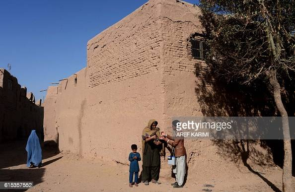 An Afghan health worker administers the polio vaccine to a child during a campaign in Herat on October 18 2016 Polio once a worldwide scourge is...