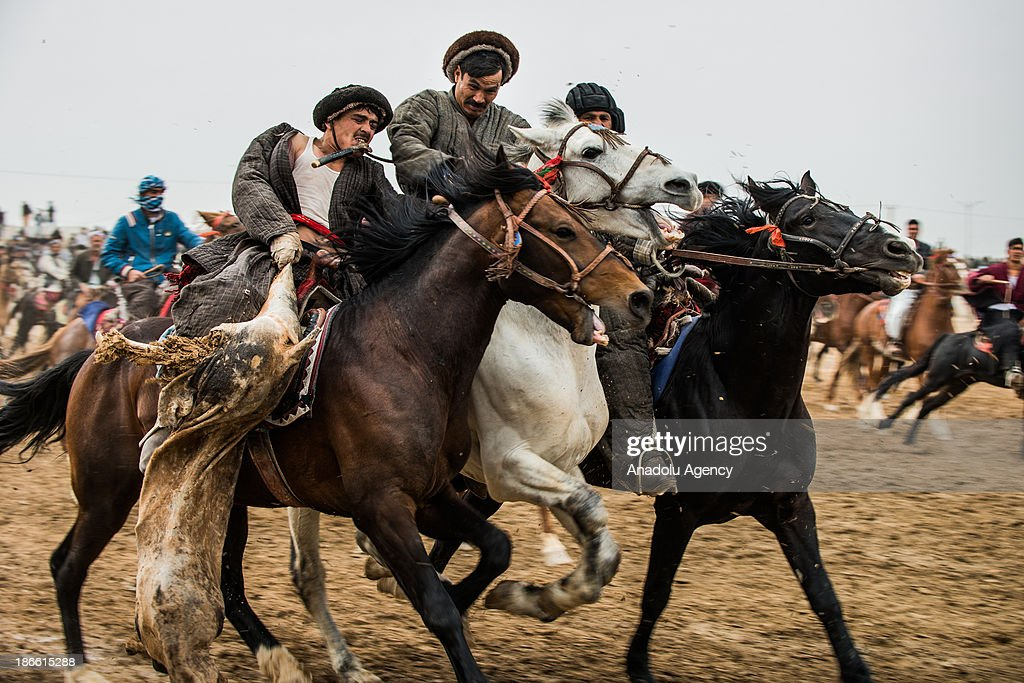 An Afghan horseman holds a calf carcass and others try to grap the goat during the Buzkashi game in Mazar-i Sharif, Afghanistan. The ancient game of Buzkashi is an Afghan national sport which is played by two teams of horsemen competing to throw an animal (calf, goat or sheep) carcass into a scoring circle. The object of the game is to get control of the carcass and bring it to the scoring area.