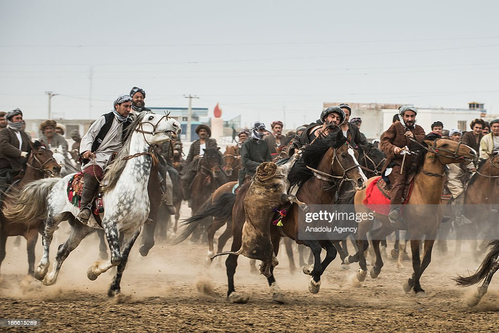 An Afghan horseman holds a calf carcass as others race for grapping it during the Buzkashi game in Mazar-i Sharif, Afghanistan. The ancient game of Buzkashi is an Afghan national sport which is played by two teams of horsemen competing to throw an animal (calf, goat or sheep) carcass into a scoring circle. The object of the game is to get control of the carcass and bring it to the scoring area.