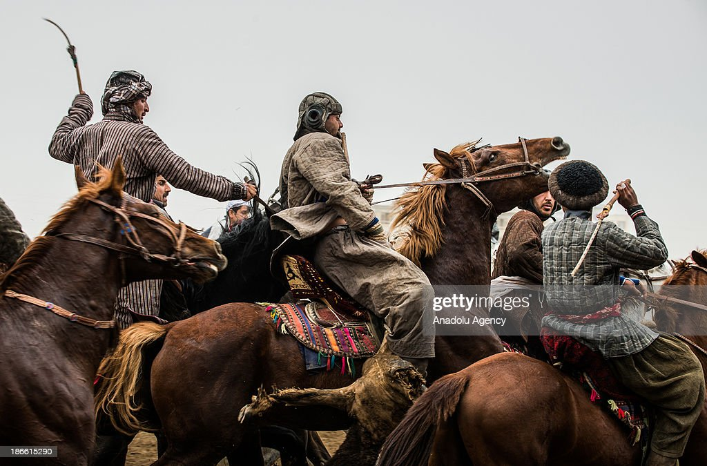 An Afghan horseman holds a calf carcass during the Buzkashi game in Mazar-i Sharif, Afghanistan. The ancient game of Buzkashi is an Afghan national sport which is played by two teams of horsemen competing to throw an animal (calf, goat or sheep) carcass into a scoring circle. The object of the game is to get control of the carcass and bring it to the scoring area.