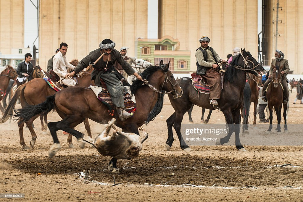 An Afghan horseman throws a calf carcass into the scoring circle during the Buzkashi game in Mazar-i Sharif, Afghanistan. The ancient game of Buzkashi is an Afghan national sport which is played by two teams of horsemen competing to throw an animal (calf, goat or sheep) carcass into a scoring circle. The object of the game is to get control of the carcass and bring it to the scoring area.