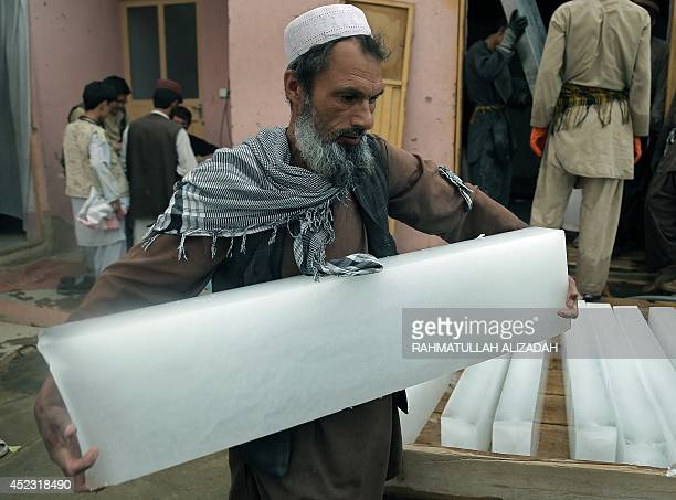 An Afghan ice vendor carries a block of ice during the holy month of Ramadan in Ghazni province on July 17 2014 Across the Muslim world the faithful...
