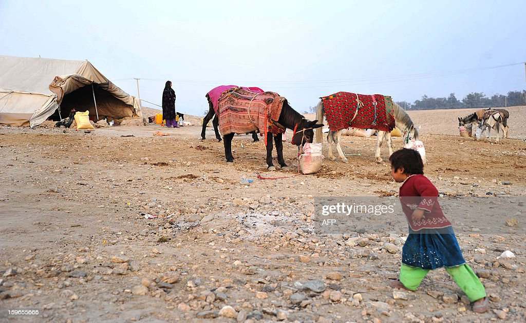 An Afghan internal refugee child walks to a tent on the outskirts of Jalalabad on January 17, 2013. In 2012 alone, spreading conflict in Afghanistan has forced more than 166,000 Afghans to flee their homes, bringing the total number of people internally displaced by conflict to at least 460,000 since the fall of the Taliban in late 2001 with conditions for the displaced falling well below international standards, according to a 2012 study by the Norwegian Refugee council. AFP PHOTO/Noorullah Shirzada