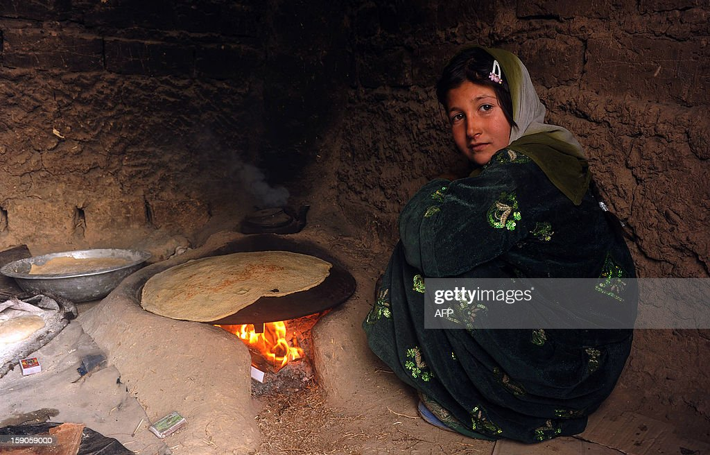 An Afghan internal refugee girl sits as she bakes bread on the outskirts of Herat on January 7, 2013. In 2012 alone, spreading conflict in Afghanistan has forced more than 166,000 Afghans to flee their homes, bringing the total number of people internally displaced by conflict to at least 460,000 since the fall of the Taliban in late 2001 with conditions for the displaced falling well below international standards, according to a 2012 study by the Norwegian Refugee council. AFP PHOTO/ Aref KARIMI