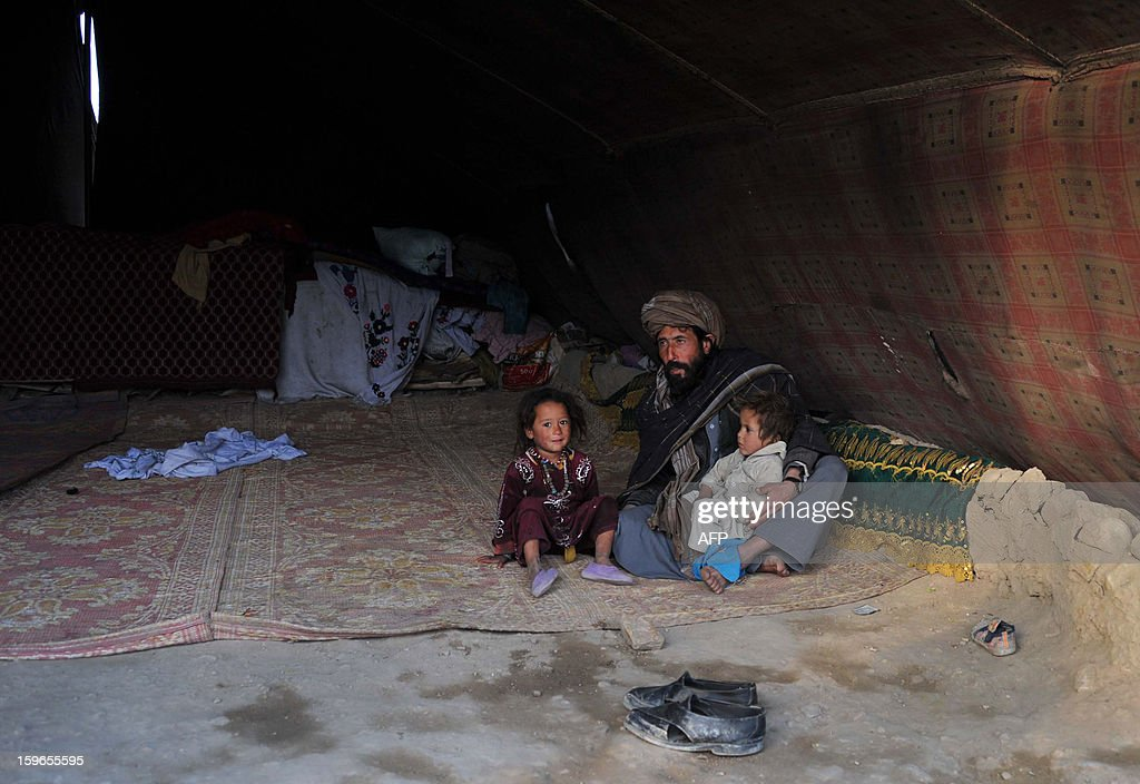 An Afghan internal refugee man sits in a tent with two children on the outskirts of Jalalabad on January 17, 2013. In 2012 alone, spreading conflict in Afghanistan has forced more than 166,000 Afghans to flee their homes, bringing the total number of people internally displaced by conflict to at least 460,000 since the fall of the Taliban in late 2001 with conditions for the displaced falling well below international standards, according to a 2012 study by the Norwegian Refugee council. AFP PHOTO/Noorullah Shirzada