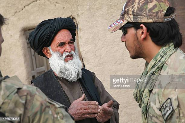 An Afghan interpreter with the US Army's 4th squadron 2d Cavalry Regiment helps to question a villager during a joint patrol with soldiers from the...