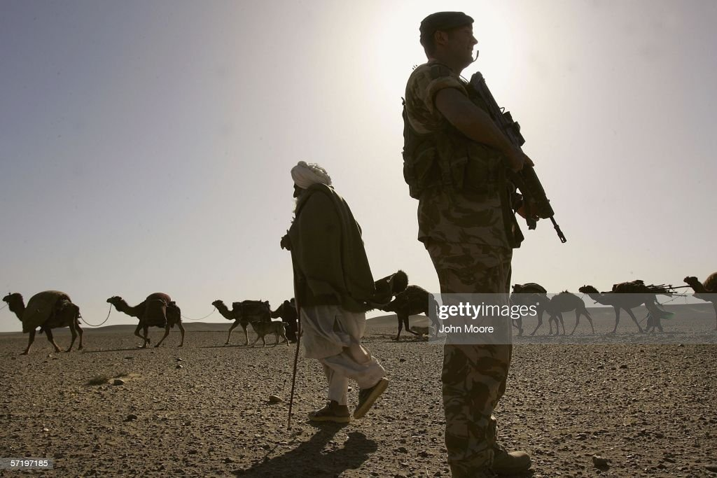 An Afghan Kuchi nomad walks with his herd of camels past a British commando from the 42 Royal Marines near Camp Bastion March 28 2006 in the desert...