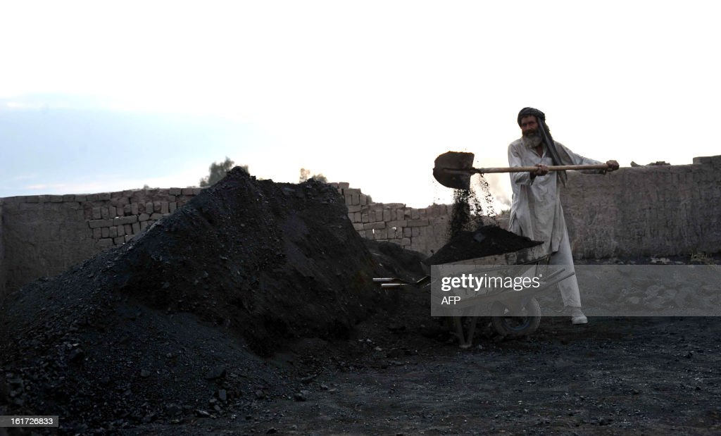 An Afghan labourer adds coal to a wheelbarrow at a traditional brick factory on the outskirts of Jalalabad on February 14, 2013. Over a third of Afghans are living in abject poverty, as those in power are more concerned about addressing their vested interests rather than the basic needs of the population, a UN report said. AFP PHOTO/ Noorullah Shirzada