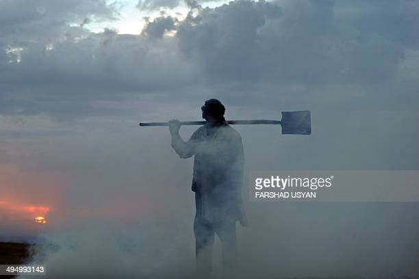 An Afghan labourer holds a shovel over his shoulders as he works at a chalk factory on the outskirts of Mazarisharif on May 31 2014 Afghanistan's...