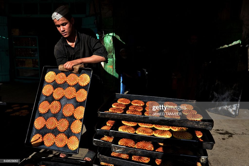 An Afghan labourer makes cookies at a traditional cookie factory in Kandahar on June 29, 2016, during the Islamic month of Ramadan. Throughout the month devout Muslims must abstain from food, drink and sex from dawn until sunset when they break the fast with the Iftar meal. / AFP / JAWED