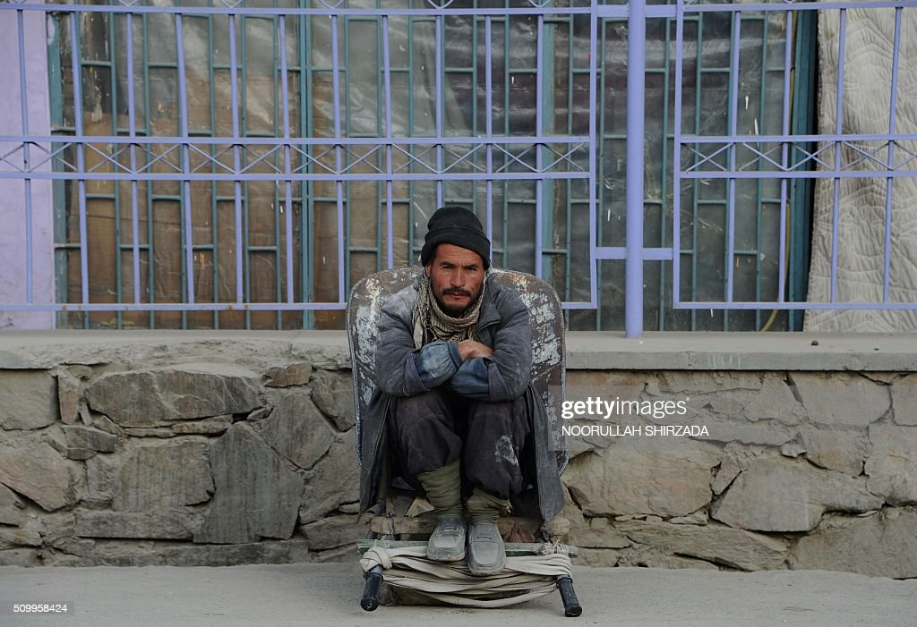 An Afghan labourer sits on his wheelbarrow as he waits for work at the roadside in Kabul on February 13, 2016. AFP PHOTO / Noorullah Shirzada / AFP / Noorullah Shirzada