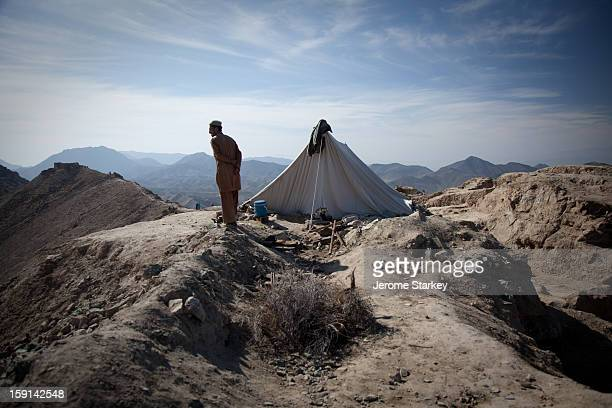 CONTENT] An Afghan labourer surveys the Mes Aynak archeological dig on the site of an ancient Buddhist settlement from outside his hilltop tent...