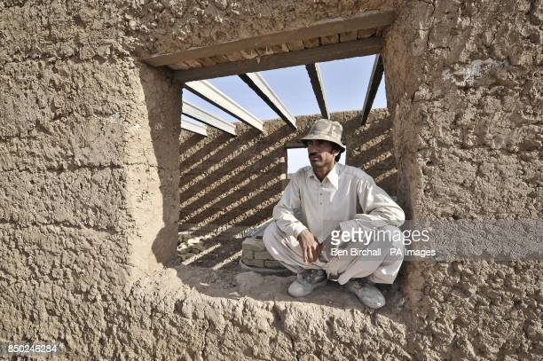 An Afghan local national construction worker takes a break and watches his coworkers from a window aperture in a new building at Patrol Base Clifton...