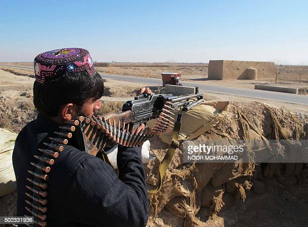 An Afghan Local Police personnel keeps watch during an ongoing battle with Taliban militants in the Marjah district of Helmand Province on December...