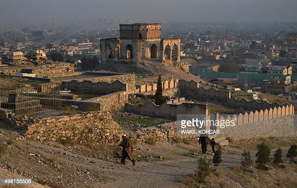 An Afghan man carries a partridge in a cage as he walks up to the Nadir Khan hilltop in Kabul on November 21 2015 AFP PHOTO / Wakil Kohsar