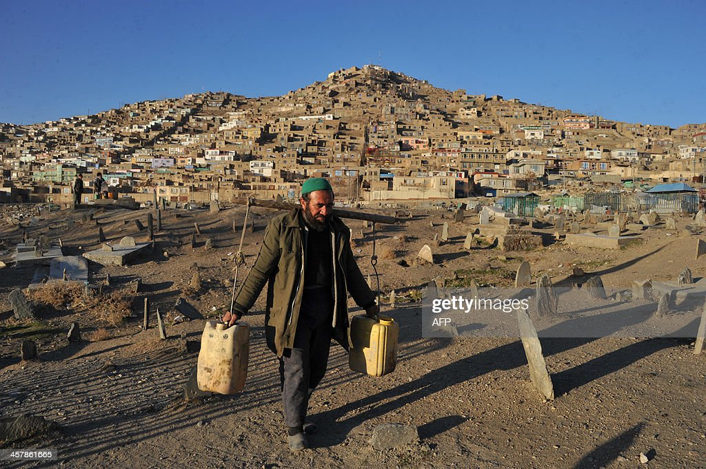 An Afghan man carries containers of water through a cemetery outside The the Kart-e-sakhi shrine in Kabul on December 19, 2013. Despite massive injection of foreign aid since the fall of the Taliban in 2001, Afghanistan remains desperately poor with some of the lowest living standards in the world. AFP PHOTO/Noorullah Shirzada