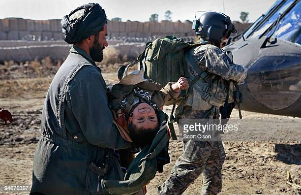 An Afghan man carries his son whose body is rigid from tetanus to a MEDEVAC helicopter behind flight medic Sgt Aaron Burrows of Amarillo Texas with C...