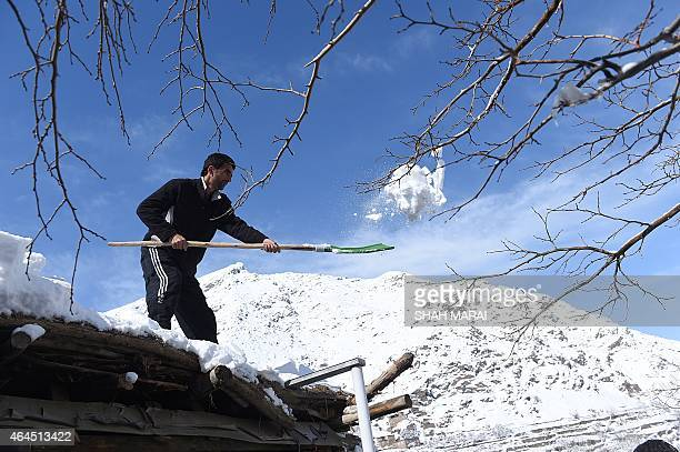 An Afghan man clears snow from his home roof top near an avalanche site at Dara Keraman district of Panjshir province north of Kabul on February 26...